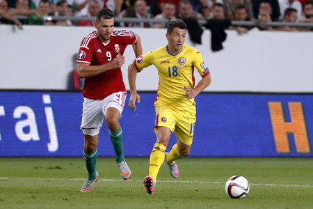 qualifier: BUDAPEST, HUNGARY - SEPTEMBER 4, 2015: Hungarian Adam Szalai (l) and Romanian Andrei Prepelita run for the ball during Hungary vs. Romania UEFA Euro 2016 qualifier football match in Groupama Arena.