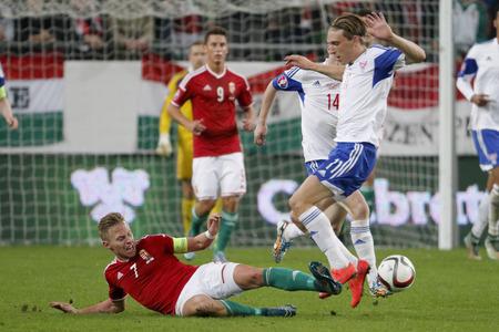 qualifier: BUDAPEST, HUNGARY - OCTOBER 8, 2015: Hungarian Balazs Dzsudzsak (l) slides against Faroese Joan Edmundsson during Hungary vs. Faroe Islands UEFA Euro 2016 qualifier football match in Groupama Arena.