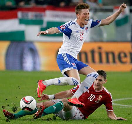 qualifier: BUDAPEST, HUNGARY - OCTOBER 8, 2015: Hungarian Zoltan Gera (r) slides against Faroese Kaj Bartalsstovu during Hungary vs. Faroe Islands UEFA Euro 2016 qualifier football match in Groupama Arena.