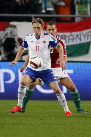 qualifier: BUDAPEST, HUNGARY - OCTOBER 8, 2015:From  Hungarian Roland Juhasz (r) covers the ball Faroese Joan Edmundsson during Hungary vs. Faroe Islands UEFA Euro 2016 qualifier football match in Groupama Arena.