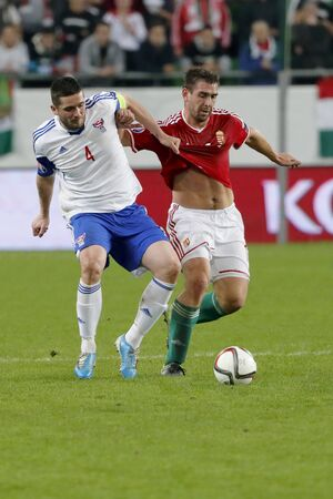 qualifier: BUDAPEST, HUNGARY - OCTOBER 8, 2015: Hungarian Daniel Bode (r) is pulled back by Faroese Atli Gregersen during Hungary vs. Faroe Islands UEFA Euro 2016 qualifier football match in Groupama Arena.