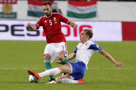 qualifier: BUDAPEST, HUNGARY - OCTOBER 8, 2015: Hungarian Attila Fiola (l) is tackled by Faroese Joan Edmundsson during Hungary vs. Faroe Islands UEFA Euro 2016 qualifier football match in Groupama Arena.