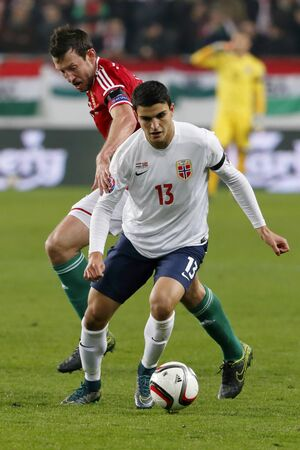 qualifier: BUDAPEST, HUNGARY - NOVEMBER 15, 2015: Hungarian Akos Elek l runs after Norwegian Mohamed Elyounoussi during Hungary vs. Norway UEFA Euro 2016 qualifier play-off football match at Groupama Arena. Editorial