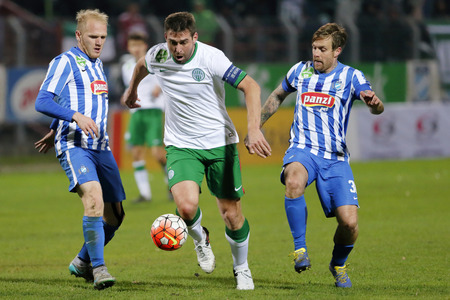 BUDAPEST, HUNGARY - NOVEMBER 21, 2015: Daniel Bode of Ferencvaros runs between Patrik Poor (l) and Adam Vass (r) of MTK during MTK Budapest - Ferencvaros OTP Bank League football match at Illovszky Stadium.