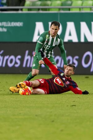 BUDAPEST, HUNGARY - FEBRUARY 10, 2016: Tamas Hajnal of Ferencvaros (l) is tackled by Mate Patkai of Videoton during Ferencvaros - Videoton Hungarian Cup quarter final football match at Groupama Arena.