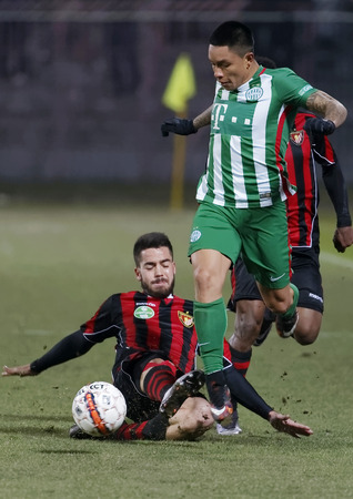 cristian: BUDAPEST, HUNGARY - FEBRUARY 27, 2016: Endre Botka of Honved (l) tries to slide against Cristian Ramirez of Ferencvaros during Budapest Honved - Ferencvaros OTP Bank League football match at Bozsik Stadium. Editorial