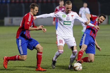 vasas: BUDAPEST, HUNGARY - MARCH 8, 2016: Zsolt Korcsmar (l) and Kire Ritevski (r) of Vasas tries to stop Zsolt Horvath of DVSC during Vasas - DVSC-TEVA OTP Bank League football match at Illovszky Stadium. Editorial
