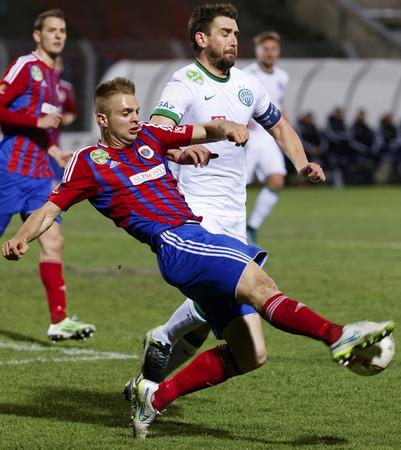 vasas: BUDAPEST, HUNGARY - MARCH 19, 2016: Danijel Romic of Vasas (l) saves the ball from Daniel Bode of Ferencvaros during Vasas - Ferencvaros OTP Bank League football match at Illovszky Stadium.
