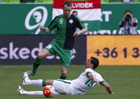 BUDAPEST, HUNGARY - APRIL 6, 2016: Leandro De Almeida of Ferencvaros (r) slide tackles Tamas Koltai of Paks during Ferencvaros - Paks OTP Bank League football match at Groupama Arena.