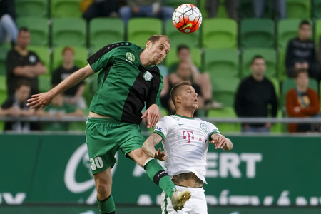 BUDAPEST, HUNGARY - APRIL 6, 2016: Roland Varga of Ferencvaros (r) duels for the ball with Janos Szabo of Paks int he air during Ferencvaros - Paks OTP Bank League football match at Groupama Arena.