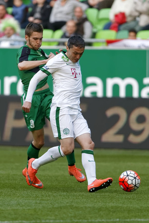 teammate: BUDAPEST, HUNGARY - APRIL 6, 2016: Vladan Cukic of Ferencvaros (r) covers the ball from Janos?Hahn of Paks during Ferencvaros - Paks OTP Bank League football match at Groupama Arena. Editorial
