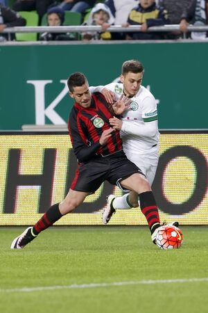 teammate: BUDAPEST, HUNGARY - APRIL 10, 2016: Andras Rado of Ferencvaros (r) battles for the ball with Endre Botka of Honved during Ferencvaros - Budapest Honved OTP Bank League football match at Groupama Arena. Editorial