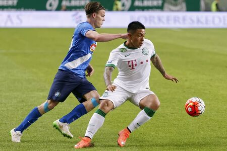 teammate: BUDAPEST, HUNGARY - APRIL 16, 2016: Cristian Ramirez of Ferencvaros (r) duels for the ball with Daniel Gera of MTK Budapest during Ferencvaros - MTK Budapest OTP Bank League football match at Groupama Arena.