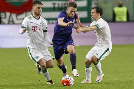 BUDAPEST, HUNGARY - APRIL 23, 2016: Kylian Hazard of Ujpest breaks out between Andras Rado (l) and Tamas Hajnal (r) of Ferencvaros during Ferencvaros - Ujpest OTP Bank League football match at Groupama Arena.