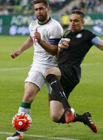 bode: BUDAPEST, HUNGARY - APRIL 23, 2016: Daniel Bode of Ferencvaros (l) fights for the ball with goalie Szabolcs Balajcza of Ujpest during Ferencvaros - Ujpest OTP Bank League football match at Groupama Arena.