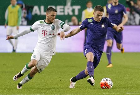 overtaken: BUDAPEST, HUNGARY - APRIL 23, 2016: Andras Rado of Ferencvaros (l) is overtaken by Kylian Hazard of Ujpest during Ferencvaros - Ujpest OTP Bank League football match at Groupama Arena.