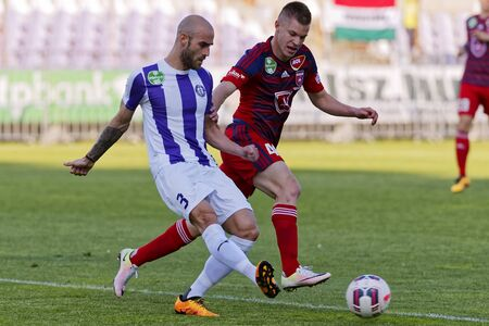 teammate: BUDAPEST, HUNGARY - APRIL 30, 2016: Jonathan Heris of Ujpest (l) duels for the ball with Krisztian Geresi of Videoton during Ujpest - Videoton OTP Bank League football match at Szusza Stadium. Editorial