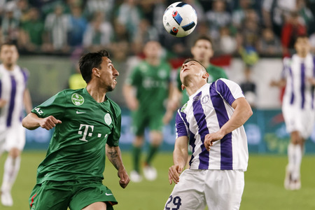 b ball: BUDAPEST, HUNGARY - MAY 7, 2016: Enis Bardhi (R) of Ujpest FC and Leandro De Almeida (L) of Ferencvarosi TC watch the ball in the air during the Hungarian Cup Final football match between Ujpest FC and Ferencvarosi TC at Groupama Arena on May 7, 2016 in B