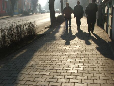 three people shadow on a paved street