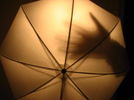 photography session: photo umbrella with hand shadow Stock Photo