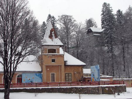 old church in winter scenery with a wooden house and trees in the background Stock Photo