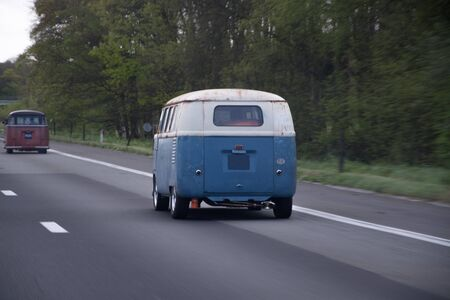 Old blue and white car driving down the highway Stock Photo