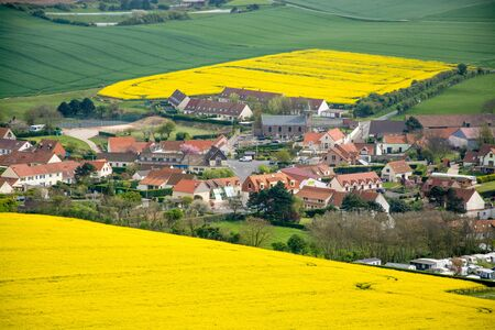 rural village in Transylvania with blooming canola flowers