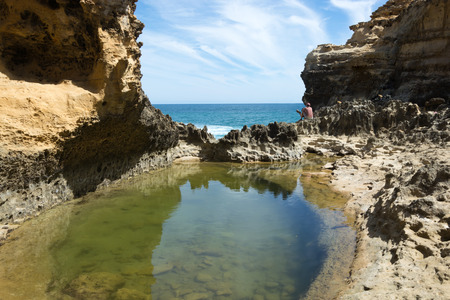 washed out: Washed out cliff side reflecting in a pool of green seawater