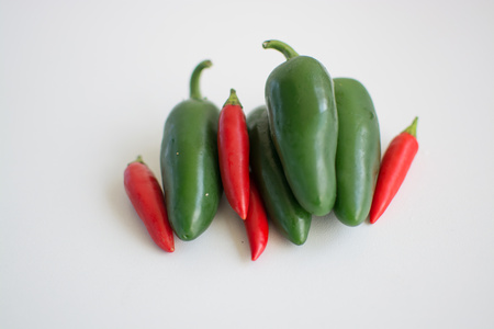 capsaicin: Bright green jalapeno hot peppers and birdseye chilli peppers on white background
