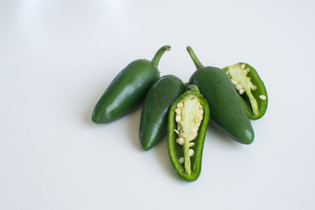 birdseye: Bright green jalapeno hot peppers and birdseye chilli peppers on white background