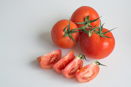 truss: Juicy ripe truss tomato and slices isolated on white background