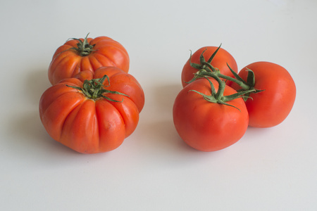 truss: Juicy ripe beefsteak and truss tomatoes side by side comparison isolated on white background