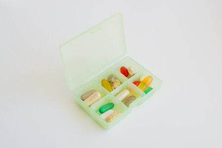 investigated: Different medicine tablets in a pill box on white background