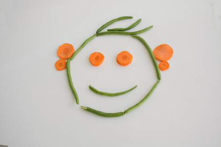 ejotes: BoyGirl face formed out of green beans and carrots Foto de archivo