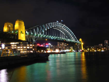 bustle: Night time view of Sydney harbor and landmarks