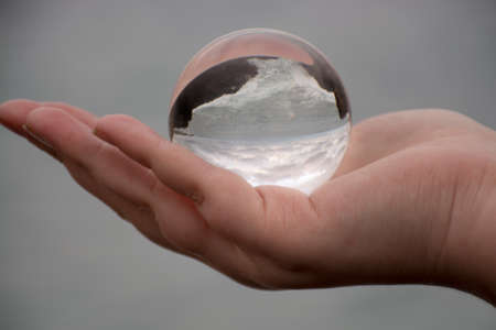 cusp: Woman holding a crystal ball reflecting the seaside Stock Photo