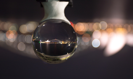 Night time view of Sydney harbour bridge and surrounds reflecting in a crystal ball