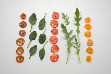 baby spinach: Three types of cherry tomato slices with baby spinach and roquette (arugula) leaves forming a deconstructed salad Stock Photo