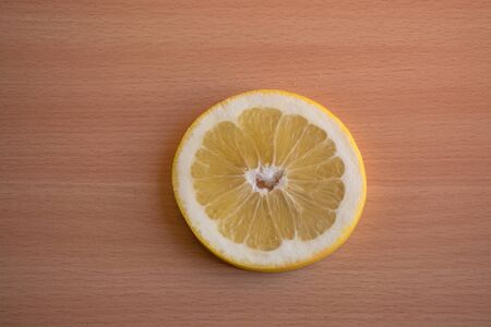 One slice of yellow grapefruit on a wooden background