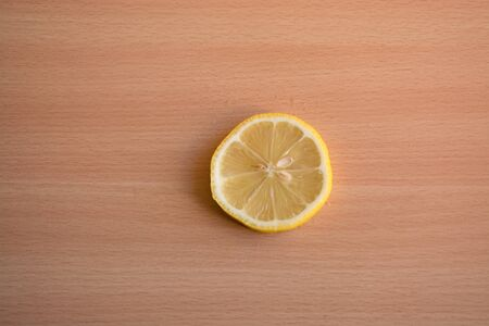 One slice of lemon on a wooden background Stock Photo