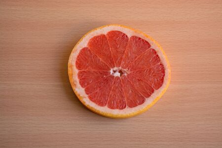 One slice of red grapefruit on a wooden background Stock Photo