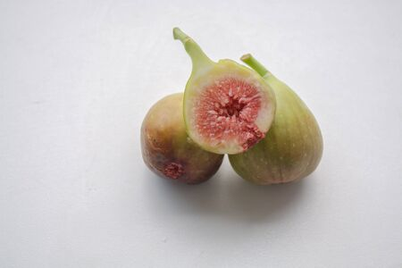 Green fresh fig fruit whole and cross section on a light background