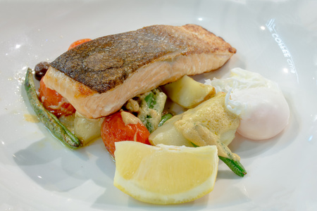 Salmon steak with poached egg and grilled vegetables and mustard sauce