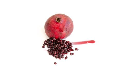 Ripe red pomegranate with seeds scattered next to it Stock Photo