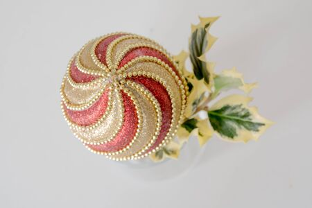 Closeup of a swirly red and gold Christmas ornament with holly