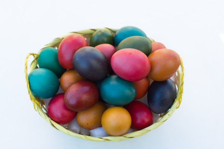 basket of natural easter eggs on white background - top view