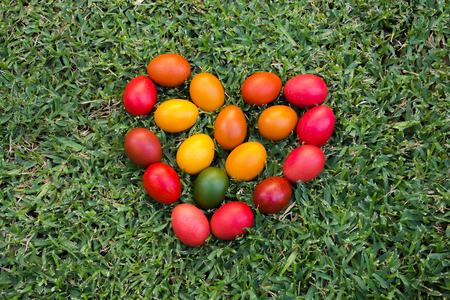 colourful Easter eggs in grass arranged as a love heart