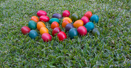 colourful Easter eggs in grass scattered in a random pattern