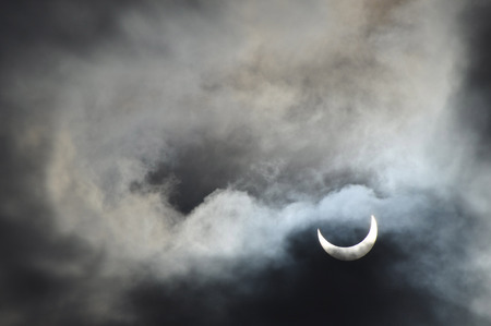 apogee: Partial solar eclipse with the clouds Stock Photo