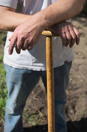 relying: A man relying on a garden spade in the sun, with arms crossed. Stock Photo